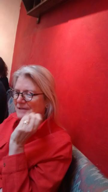 Ann Hagadorn, shown here at Coupa Cafe in Palo Alto, in red, she and the room, has written an important book about privatization of the military in U.S.